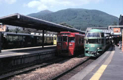 Yufuin station on the Kyūdai main line, Kyūshū, with two tokkyū trains.  The one on the right is the all-reserved Yufuin-no-mori, with 'panorama seats'.  On the extreme left is a 'torokko' train with open sides, not shown in the timetable.